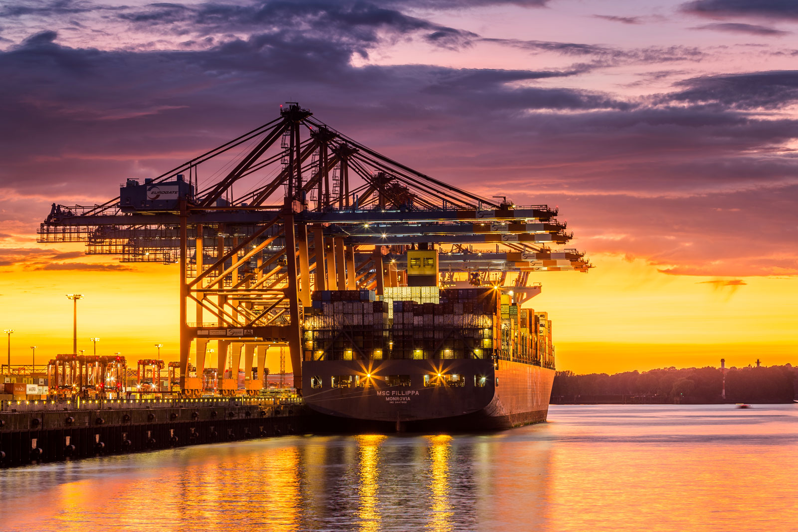 Ein Containerschiff bei Sonnenuntergang im Hamburger hafen