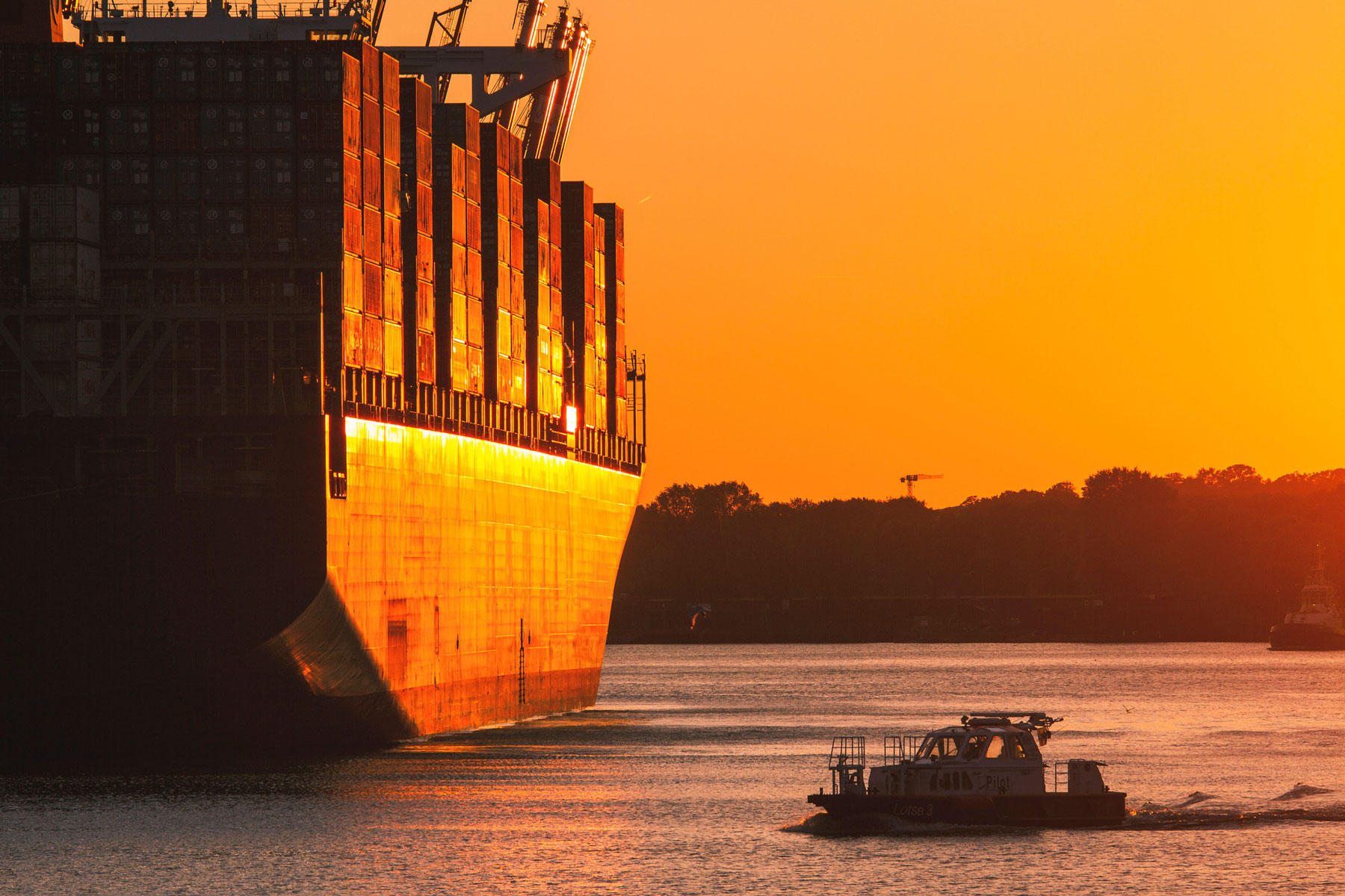 Containerschiff bei Sonnenuntergang in Hamburg