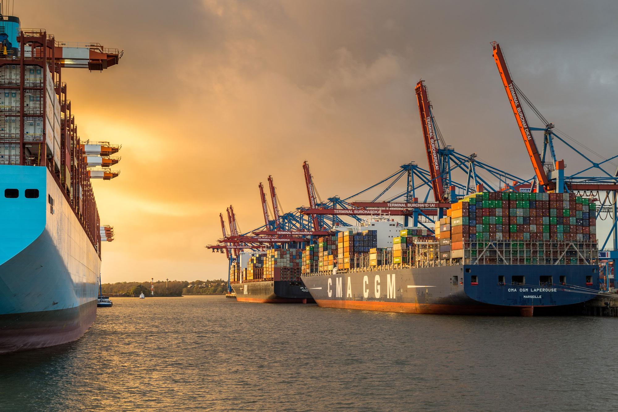 Sonnenuntergang im Hamburger Hafen mit mehreren Containerschiffen